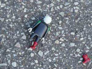 zerbrochenes Playmobilmännchen auf Asphalt