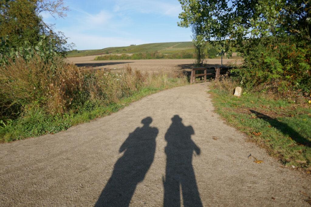 Zwei Gestalten als Schatten auf dem Weg