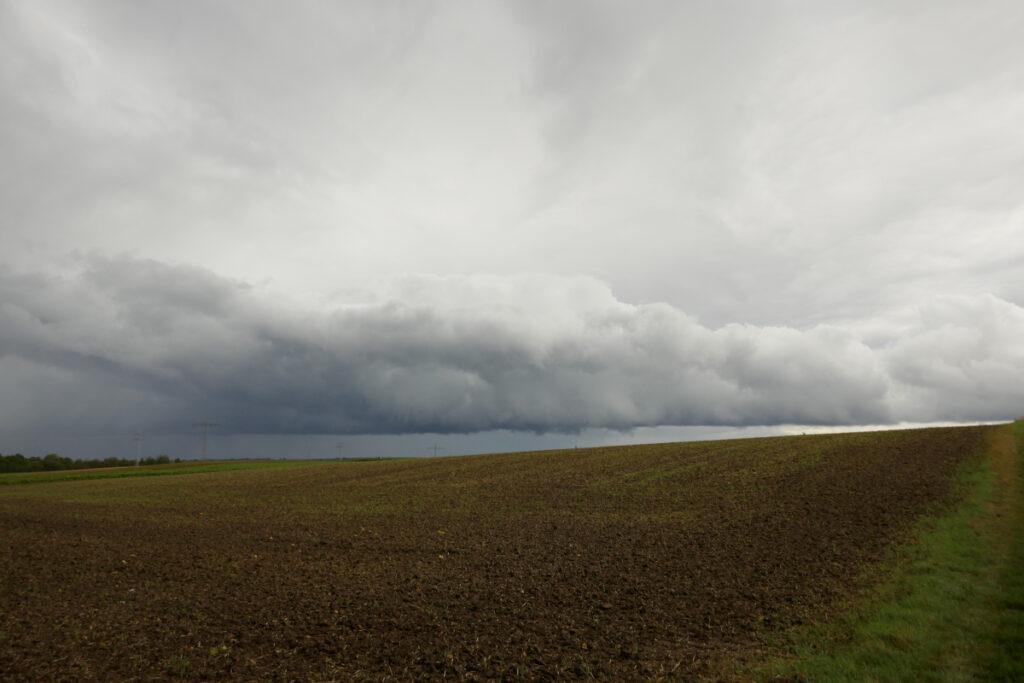 Wolkenwand und Regen über Acker
